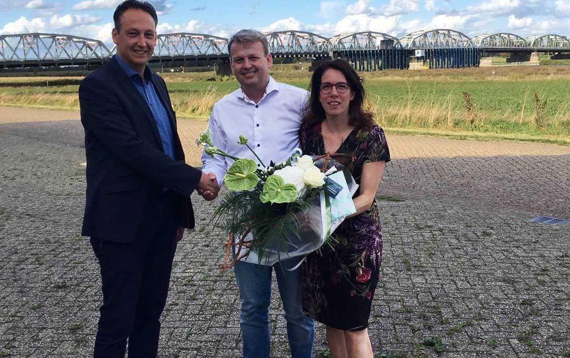 Man feliciteert man en vrouw met afsluiten financiering met een bos bloemen en bioscoopbon. Achtergrond brug Grave.